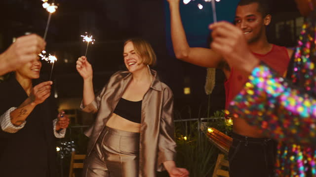 smiling female and male friends dancing in party at patio - multiracial group stock videos & royalty-free footage