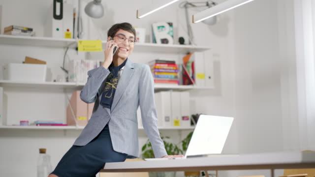 vidéos et rushes de propriétaire d'entreprise féminin de sourire ayant un appel d'affaires - répondre