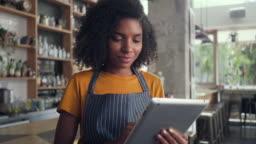 A smiling female cafe owner using digital tablet