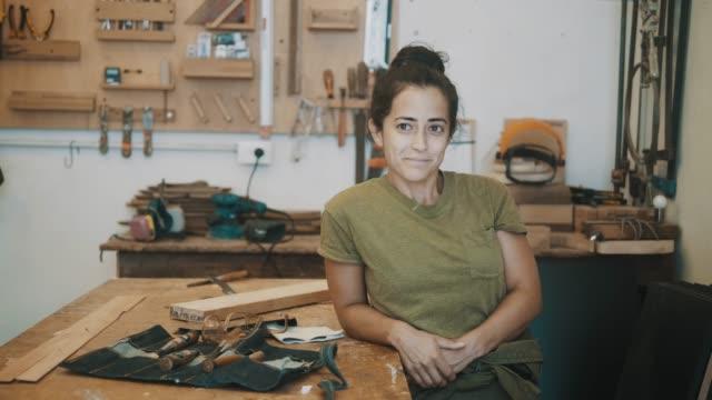stockvideo's en b-roll-footage met glimlachende vrouwelijke timmerman bij workshop - kunstnijverheid