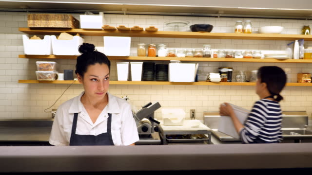 vídeos de stock e filmes b-roll de ms smiling female chef listening to question from coworker while preparing for dinner service in restaurant kitchen - cozinha industrial