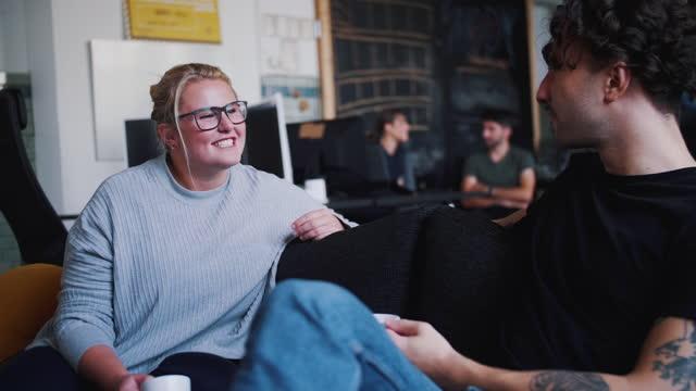 smiling female computer talking with male colleague while having coffee in coworking office - kollega bildbanksvideor och videomaterial från bakom kulisserna