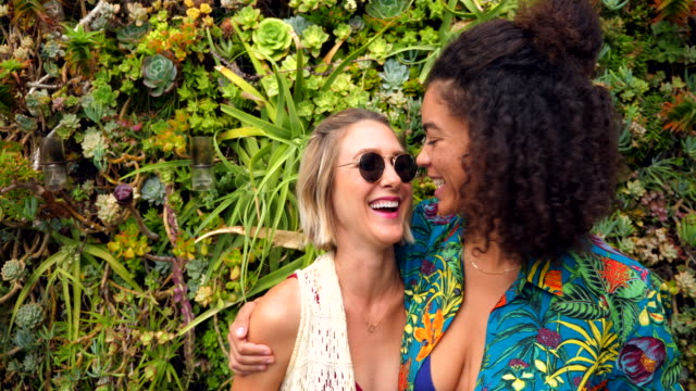ms smiling female couple kissing and embracing in front of living wall - environmentalist stock videos & royalty-free footage