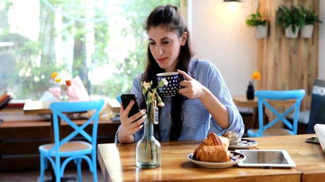 Lächelnde Kundin mit Handy im Cafe