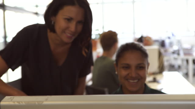 smiling female design professionals discussing over desktop pc at office - colleague stock videos & royalty-free footage