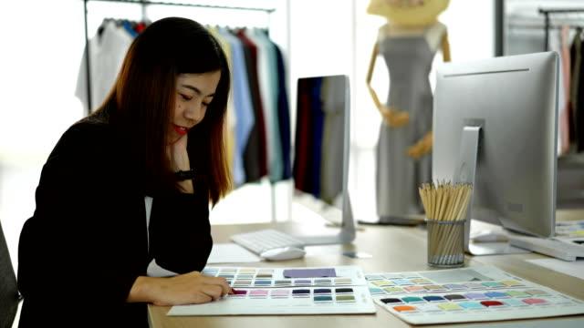 オフィスで彼女の服の製品のための色を選択する4k笑顔の女性デザイナー - 生地サンプル点の映像素材/bロール