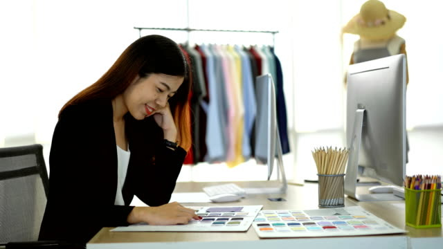 smiling female designer looking at fabric swatch in the office - color swatch stock videos & royalty-free footage