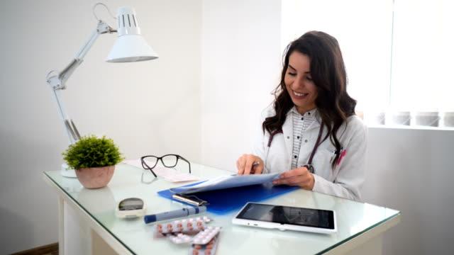 笑顔の女性医師の医療記録保持 - クリップボード点の映像素材/bロール