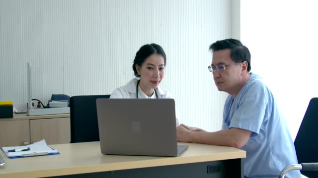 smiling female doctor talking with senior patient in clinic - part of a series stock videos & royalty-free footage