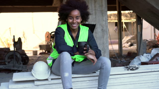 smiling female engineer holding coffee at construction site - females stock videos & royalty-free footage