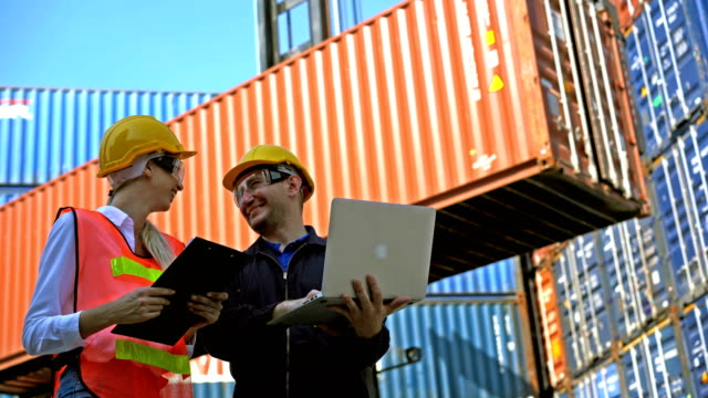 4k smiling female engineer in protective uniform holding clipboard discussing with her colleague during working in front of shipping cargo container stacks at shipping dock - docker stock videos & royalty-free footage