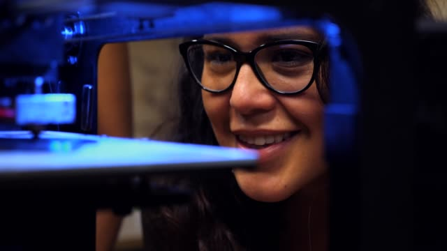 vídeos de stock e filmes b-roll de cu zi smiling female engineer watching prototype being printed on 3d printer in workshop - stem assunto