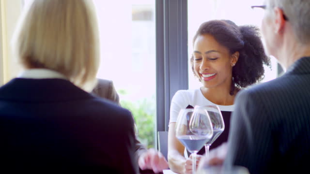 ms smiling female executives sitting in restaurant having a meeting over lunch. - meal stock videos and b-roll footage