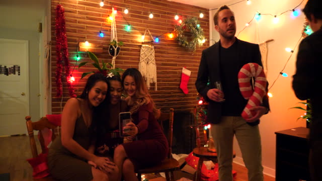 ms smiling female friends dancing while posing for selfie during holiday party in home - cross legged stock videos & royalty-free footage