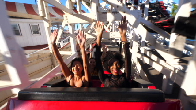 ms smiling female friends riding roller coaster with arms raised in air - rollercoaster stock videos & royalty-free footage