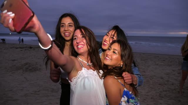 vídeos y material grabado en eventos de stock de ms smiling female friends taking selfie with smart phone during beach party on summer evening - amistad femenina