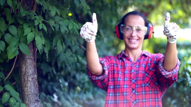 smiling female gardener showing thumbs up - ear protectors stock videos and b-roll footage