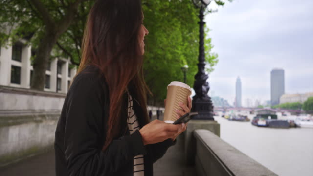 Smiling female in London with her coffee texting with mobile phone by the Thames