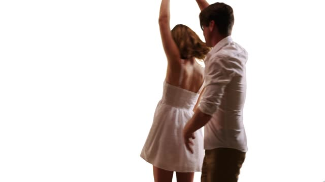 smiling female in white sundress dancing with romantic boyfriend in studio - サンドレス点の映像素材/bロール