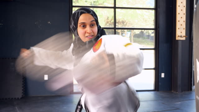 ms smiling female muslim self defense instructor demonstrating kick during class in gym - hijab stock videos & royalty-free footage
