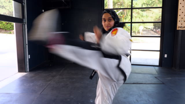 ms smiling female muslim self defense instructor demonstrating kick in gym - traditional clothing stock videos & royalty-free footage