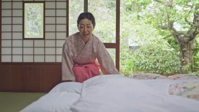 Smiling female owner laying futon in hotel room