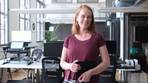 leende kvinnlig professionell med digital tablett - skrivbord bildbanksvideor och videomaterial från bakom kulisserna