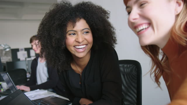 smiling female professionals working together at office. - science and technology stock videos & royalty-free footage