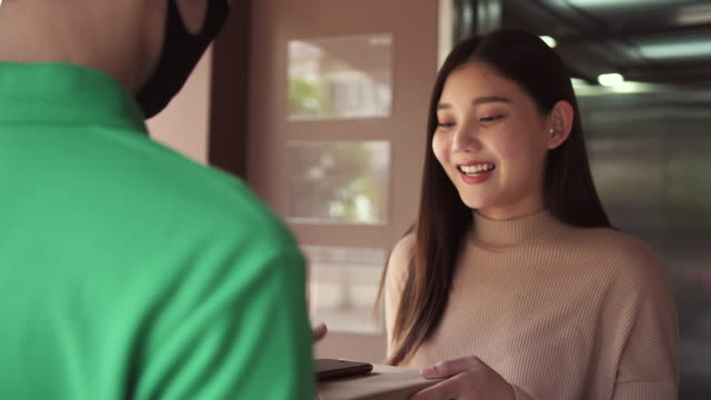 smiling female receives postal parcel and signs electronic signature deivce - south east asia stock videos & royalty-free footage