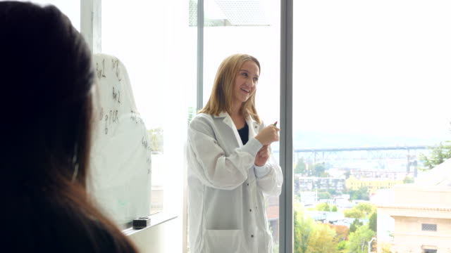 ms smiling female scientist discussing project at white board in laboratory - lab coat stock videos & royalty-free footage