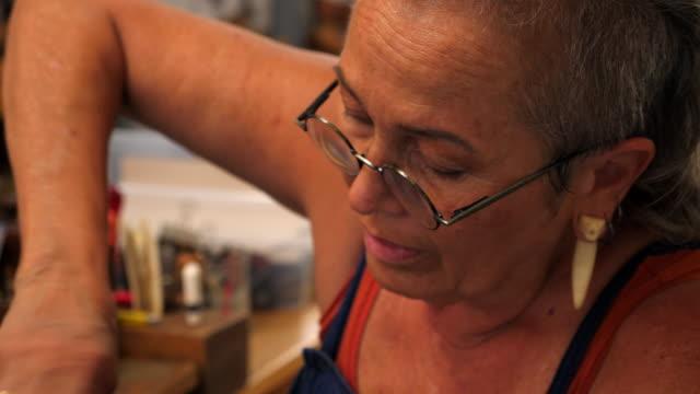 vídeos de stock, filmes e b-roll de r/f cu smiling female shoemaker hand making shoe in workshop - 55 59 anos