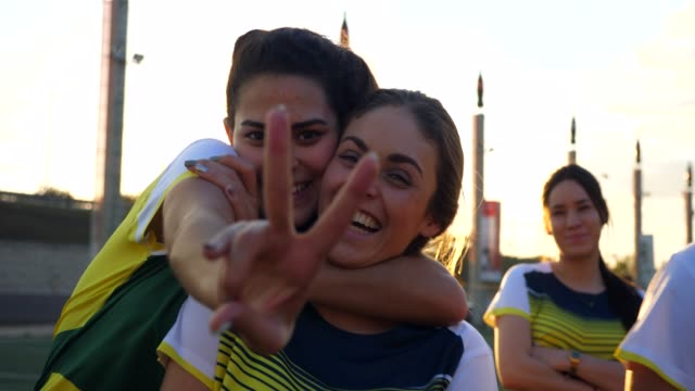 ms smiling female soccer teammates embracing on field before game - v sign stock videos & royalty-free footage