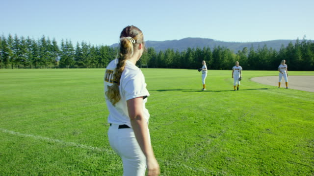 MS Smiling female softball player warming up with teammates in field before game