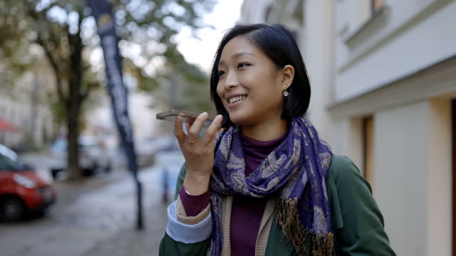 smiling female using smartphone on footpath - short hair stock videos & royalty-free footage
