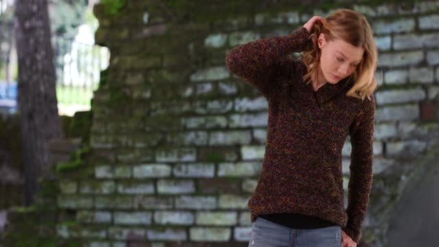 smiling female wearing sweater standing outdoors with hands in pockets in fall - hands in pockets stock videos & royalty-free footage