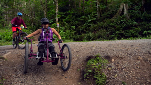 ts smiling female wheelchair athlete on adaptive mountain bike beginning ride on trail with friend - wheelchair stock videos & royalty-free footage