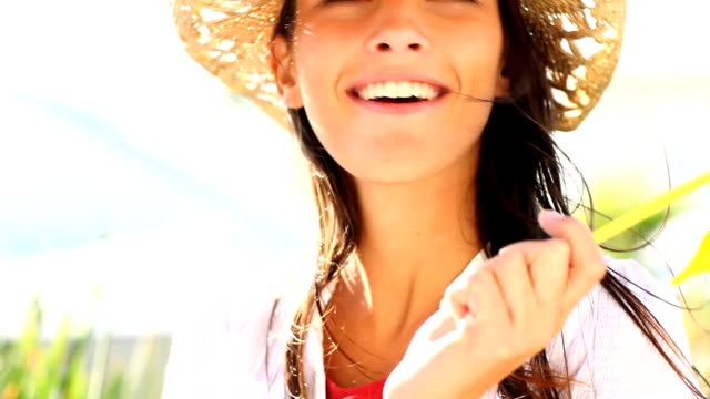 donna sorridente con una girandola e cappello per il sole - persona attraente video stock e b–roll