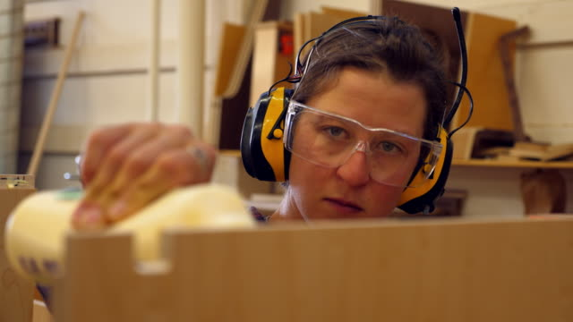 ms smiling female woodworker applying glue to edge of cabinet - glue stock videos and b-roll footage