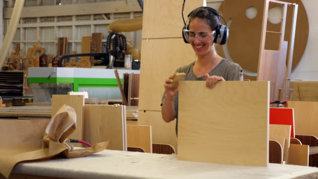 ms smiling female woodworker sanding edge of shelf while building cabinet in woodshop - craft stock videos & royalty-free footage