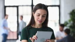 Smiling female worker involved in work on digital tablet