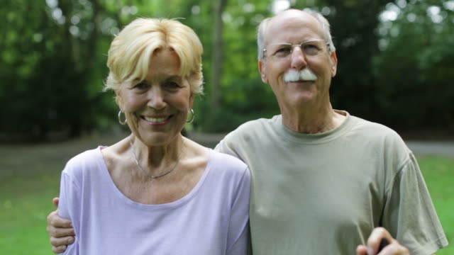 smiling fit senior couple looking at each other in park - racewalking stock videos and b-roll footage