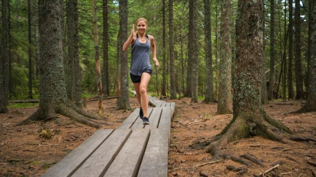 smiling fit woman running in nature, sprinting on wooden pathway through forest on beautiful summer day - approaching stock videos & royalty-free footage