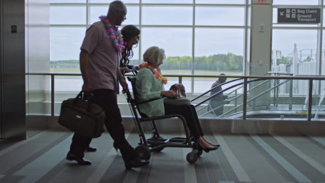 smiling flight attendant wearing lei pushes elderly woman in wheelchair through tropical airport terminal. - crew stock videos & royalty-free footage