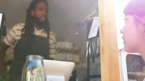 stockvideo's en b-roll-footage met cu smiling food truck owner taking order from customer - klanten georiënteerd