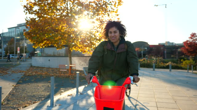 ts smiling friends commuting to work on electric bike share bikes - riding stock videos & royalty-free footage