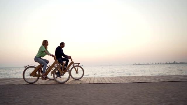 vidéos et rushes de amis souriants vélo par la mer - enjoyment