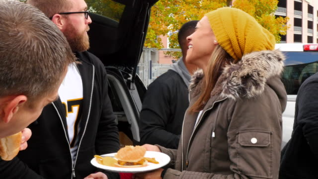 MS PAN Smiling friends eating and drinking at tailgating party before football game