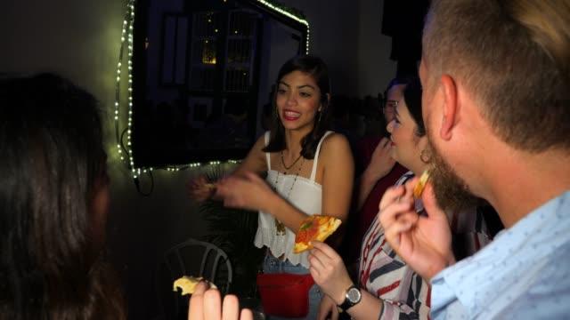vídeos y material grabado en eventos de stock de ms smiling friends enjoying pizza during party in night club - pizza