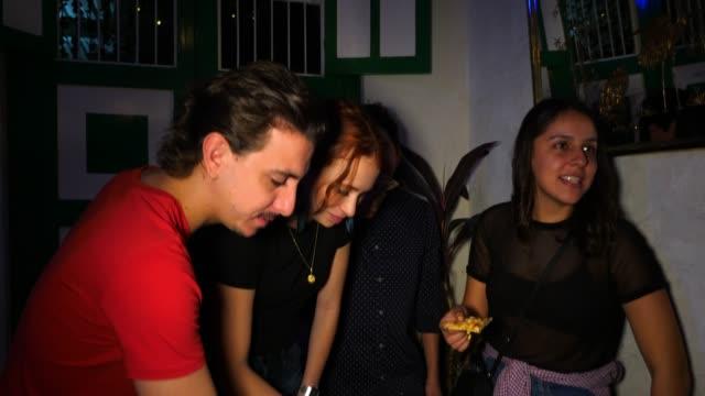 vidéos et rushes de ms smiling friends enjoying pizza during party in night club - vie sociale