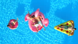 AERIAL: Smiling friends enjoying summer vacation on pizza, doughnut and flamingo